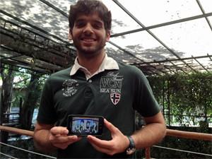 Marcelo Florêncio Sobral, de 23 anos, e o aplicativo educativo que ajudou a desenvolver (Foto: Ana Carolina Moreno/G1)