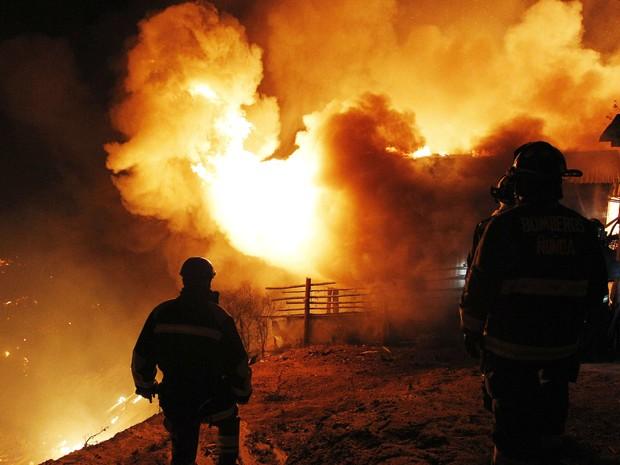 Grupo combate o fogo em área atingida por incêndio em Valparaíso, no Chile. (Foto: Eliseo Fernandez/Reuters)
