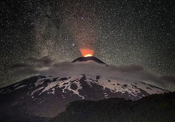 Céu estrelado e cume do vulcão com pequena erupção. O Villarica é um dos vulcões mais ativos do Chile (Foto: © Max Fercondini)