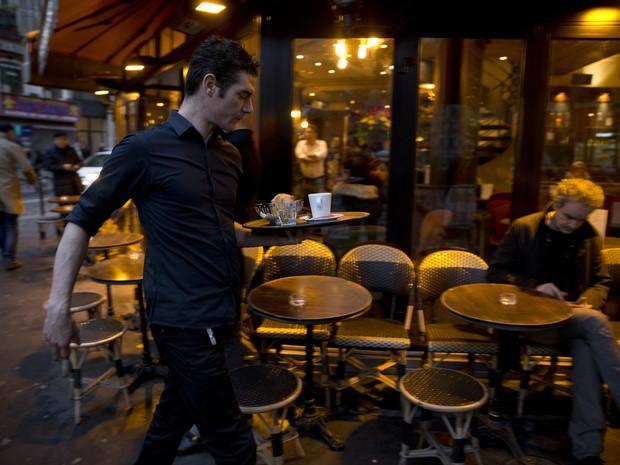 Garçom passa com bandeja no bar La Bonne Bière, alvo dos atentados em Paris que reabriu nesta sexta-feira (4) (Foto: KENZO TRIBOUILLARD / AFP)
