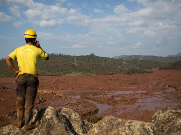 06/11 - Um funcionário da equipe de resgate observa a destruição em meio a lama após o rompimento de uma barragem de rejeitos da mineradora Samarco no Distrito de Bento Rodrigues, no interior de Minas Gerais (Foto: Felipe Dana/AP)