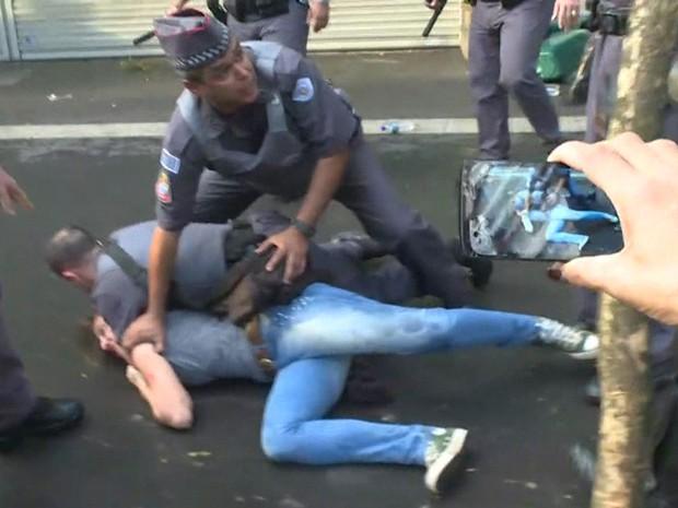 Policial militar prende uma mulher durante a manifestação na Avenida Paulista (Foto: TV Globo/Reprodução)