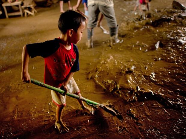Garoto ajuda o pai a limpar o local onde ficava seu barraco antes das inundações em uma província ao leste de Manila. (Foto: Nicolas Asfouri/AFP)