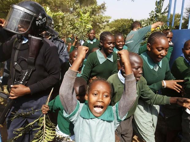 Estudantes da escola primária Langata, em Nairóbi, Quênia, correm passando por policiais durante manifestação contra um muro ilegalmente erigido por uma construtora em volta do playground da escola. A polícia dispersou o protesto com gás lacrimogêneo (Foto: Thomas Mukoya/Reuters)