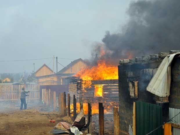 Um homem tenta salvar sua casa do fogo na aldeia de Smolenka. (Foto: Evgeny Yepanchintcev / AP Photo)
