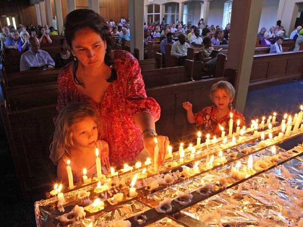 Mãe e seus filhos acendem velas durante missa em homenagem a Nelson Mandela, em Johanesburgo. (Foto: Tsvangirayi Mukwazhi / AP Photo)