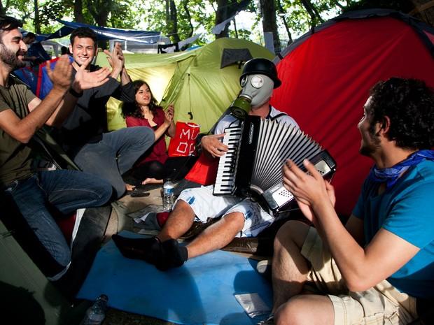 7 de junho - Jovens acampados na praça Taksim, em Istambul, cantam músicas e batem palmas comandados por um sanfoneiro com uma máscara de gás em meio às tendas (Foto: Gurcan Ozturk/AFP)