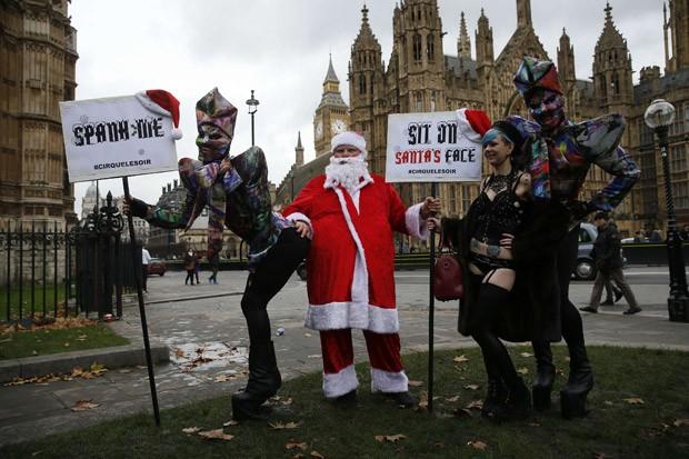 'Noel' participa de protesto contra mudanças na regulação de pornografia na Inglaterra. Nas placas, as frases: 'Bata em mim' e 'Sente-se na cara do Papai Noel' (Foto: Stefan Wermuth/Reuters)