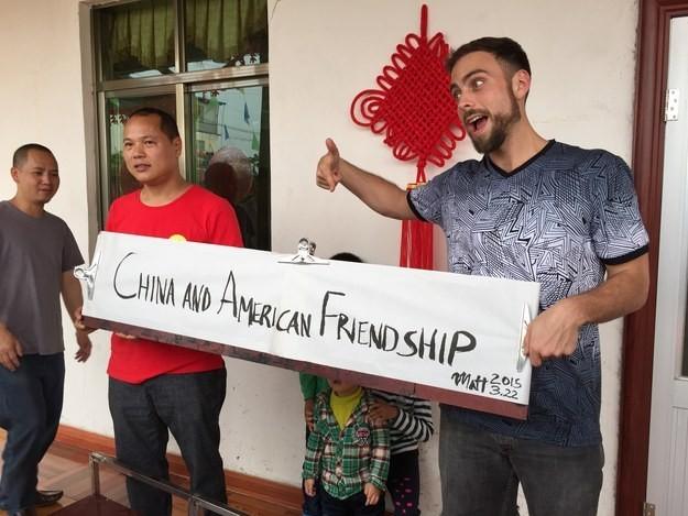 Matt e Li posam com faixa com os dizeres: 'Amizade entre a China e a América' (Foto: Qingqing Chen / BuzzFeed/ Arquivo pessoal)