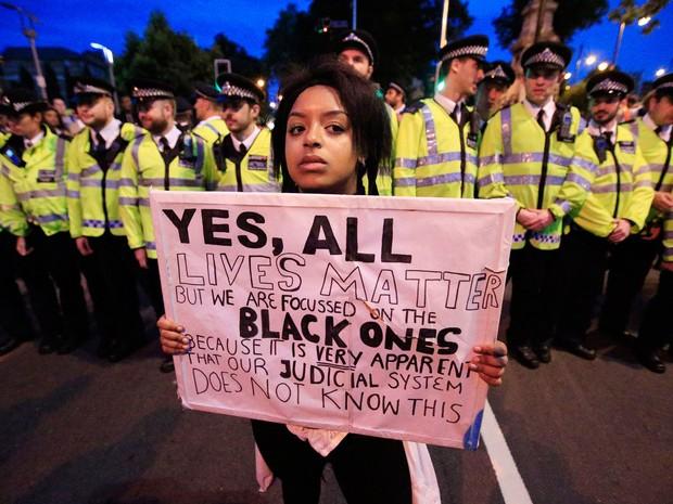 Em frente a um cordão de policiais na Brixton Road, jovem participa de manifestação em solidariedade ao movimento Black Lives Matter, em Londres, na Inglaterra, no sábado (9) (Foto: Jonathan Brady/PA via AP)