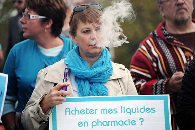Uma mulher usa um cigarro eletrônico em frente ao Parlamento Europeu, em Estrasburgo, na França, onde usuários e fabricantes do cigarro eletrônico fizeram uma manifestação.  (Foto: AFP Photo/Frederick Florin)