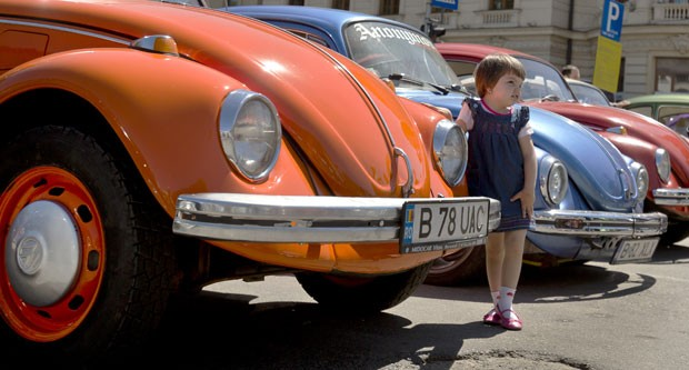 Criança faz pose ao lado do Fusca, em encontro em Bucareste (Foto: Vadim Ghirda/AP)