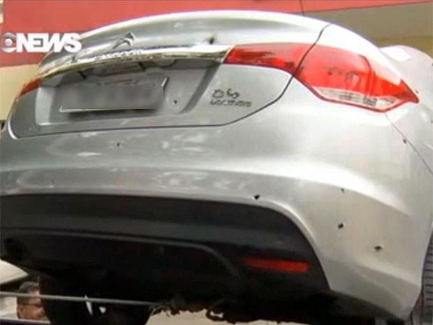 Carro do casal ficou com várias marcas de tiro (Foto: Reprodução / GloboNews)
