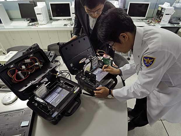 Especialistas em computadores verificam os hardwares de uma máquina infectada da rede 'KBS'. (Foto: Lee Jin-man / AP Photo)