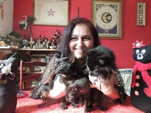 Roseli T com três de seus sete gatos pretos de estimação (Foto: Jamile Santana/G1)