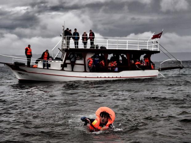 Imigrantes e refugiados chegam à ilha de Lesbos, na Grécia, após cruzar o mar Egeu vindos da Turquia (Foto: Aris Messinis/AFP)