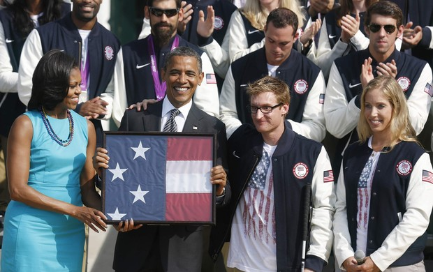 Obama e a primeira-dama Michelle seguram a bandeira americana ao lado do nadador paralímpico Brad Snyder e da esgrimista olímpica Mariel Zagunis (Foto: Reuters)