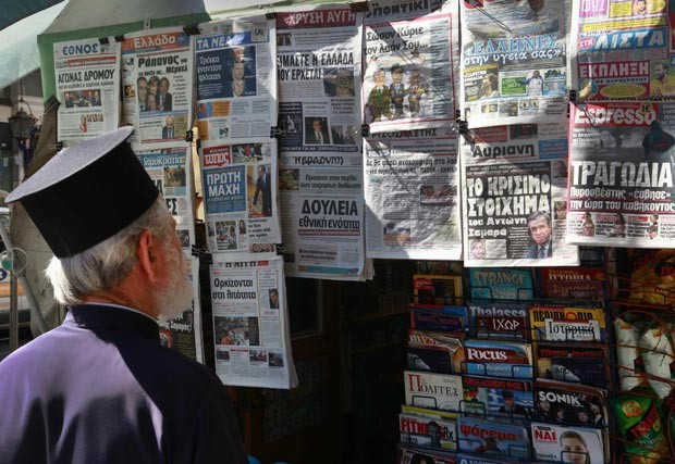 Padre ortodoxo grego lê nesta quinta-feira (21) em Atenas o noticiário sobre a formação do novo governo (Foto: AFP)