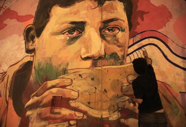Artista contra o exército egípcio e o governo trabalha em um grafite representando a vida no país em Cairo neste domingo (24) (Foto: Amr Abdallah Dalsh/Reuters)