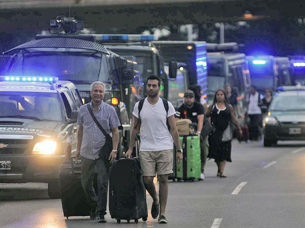 Pessoas carregam suas bagagens através de uma fila de viaturas que garantem o acesso ao aeroporto internacional Ezeiza, em Buenos Aires, na terça (22) (Foto: AFP Photo/Telam/STR)