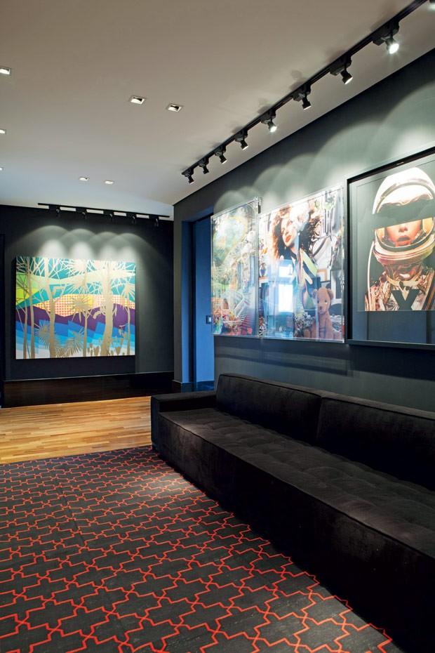 designer de interiores Diogo Oliveira expõe parte das suas obras de arte na área do closet. A luz focada vem de spots direcionados e a parede preta reforça a sensação de galeria. Projeto luminotécnico da Labluz (Foto: Lufe Gomes/Editora Globo)