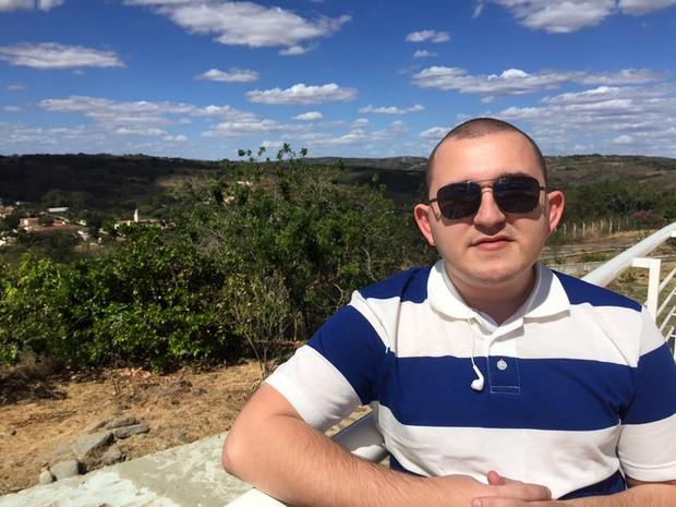 Sidney está usando óculos escuros em frente a uma paisagem com árvores bem verdes, céu azul claro com nuvens e veste uma camisa listrada azul e branca (Foto: Sidney Andrade/Arquivo Pessoal)