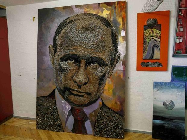 A artista ucraniana Dariya Marchenko mostra o retrato de Vladmir Putin feito com 5 mil balas; a obra se chama 'O rosto da guerra' (Foto: Gleb Garanich/Reuters)
