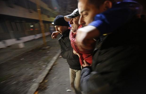 Bósnios ajudam homem que parece ferido próximo a cordão policial durante as manifestações em Tuzla, nesta quinta (6) (Foto: Amel Emric/AP)