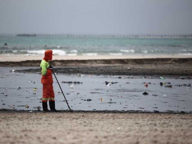 Funcionário da Slum tenta recolher lixo que é levado do riacho para o mar (Foto: Jonathan Lins/G1)