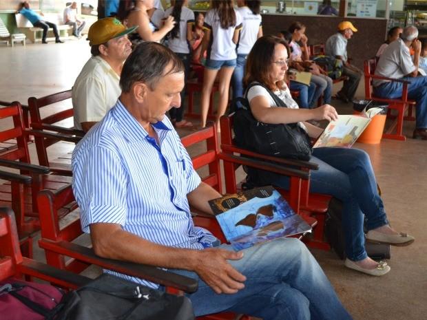 Enquanto esperava horário do ônibus, João aproveitou para ler (Foto: Magda Oliveira/ G1)
