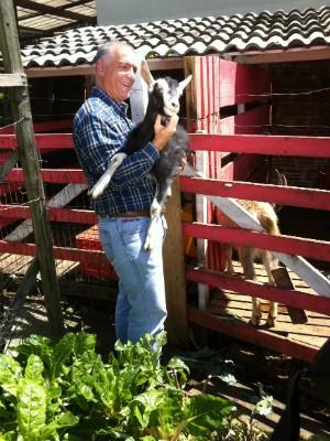 Oliver com a cabra, que se chama Grazi; pequenos animais são criados no quintal da Casa da Videira (Foto: Thais Kaniak / G1)