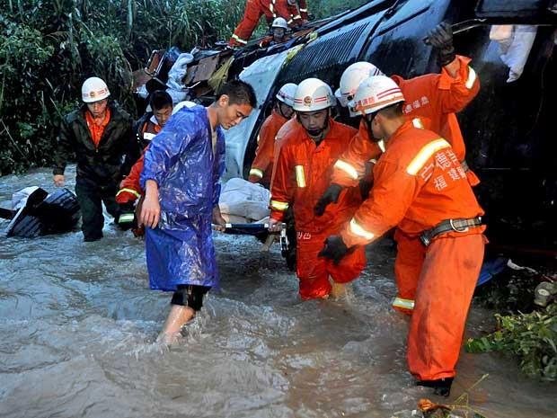 Bombeiros carregam corpo de uma vítima encontrado nos destroços de um ônibus de passageiros que caiu em um vale na província de Fujian. (Foto: AFP Photo)