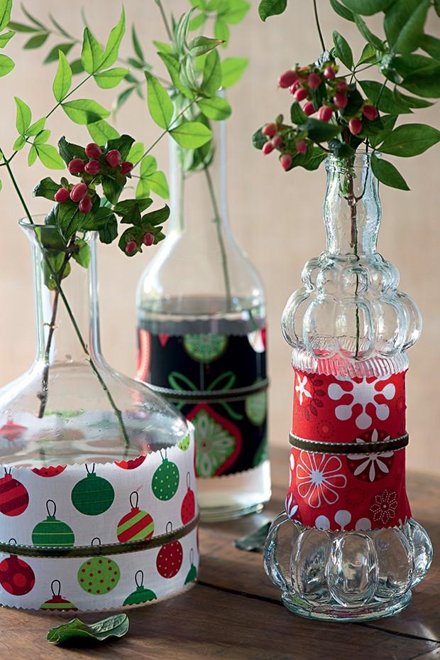 Revestidas com retalhos de tecido (grudados com fita dupla face), as garrafas se transformam em vasos perfeitos para o Natal. Para o acabamento, corte o tecido com uma tesoura zigue-zague e passe uma fita em volta do pano  (Foto: Iara Venanzi)