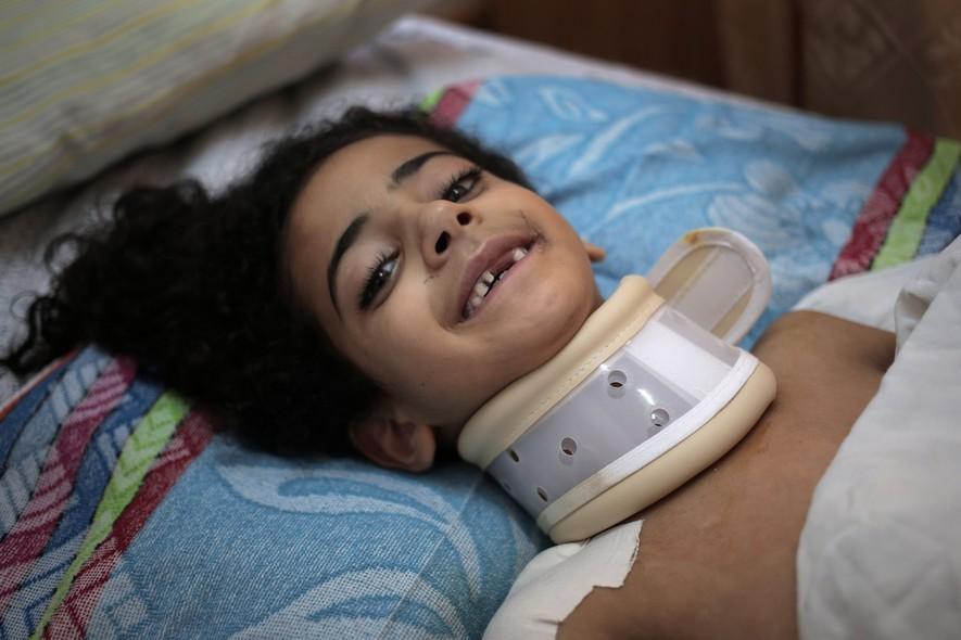 Maha al-Sheikh Khalil, de 7 anos, sorri em seu leito no hospital Shifa , onde ela está tratando a lesão feita por estilhaços em seu pescoço, que causou a paralisia de seus membros