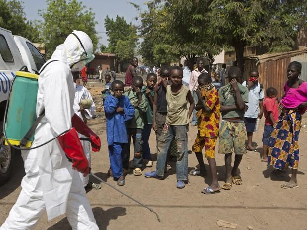 Crianças observam agente pulverizando desinfetante no lado de fora de uma mesquita como parte da luta contra o Ebola, em Bamako, no Mali, no início de novembro (Foto: Joe Penney/Reuters)