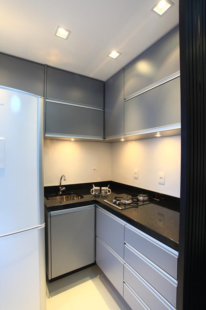 A tonalidade de cinza quebra o branco e os armários até o teto aproveitam cada espaço (Foto: Divulgação)