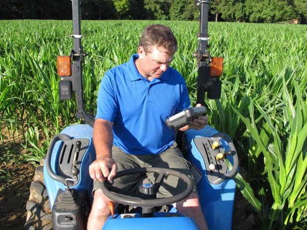 Timothy Day observa computador com GPS ao realizar desenho em plantação de milho (Foto: Allen G. Breed/AP)