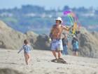 Sem camisa, Orlando Bloom se diverte soltando pipa com o filho