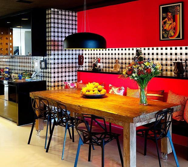 Na sala de almoço, mesa de madeira de demolição com cadeiras One, de Konstantin Grcic. O pendente é da carioca Prolight. As paredes trazem uma energética combinação de pastilhas da Jatobá (paginação exclusiva, desenhada por Rosenbaum) e parede fluorescente pink, pintada com a tinta americana rosco (Foto: The Selby)