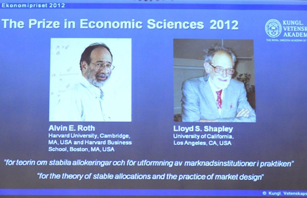 Tela mostra fotos dos ganhadores do Prêmio Nobel de economia nesta segunda-feira (15), em Estocolmo (Foto: AFP)