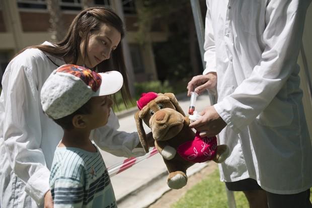 Menino ajuda a 'dar injeção' em ursinho de pelúcia, em hospital de Israel (Foto: Reuters/Amir Cohen)