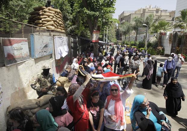 Eleitores fazem fila para votar segurando a bandeira nacional no Cairo, no Egito, nesta segunda-feira (26) (Foto: Amr Nabil/AP)