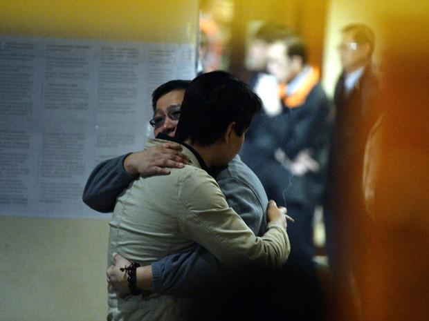 Parentes de passageiros que estavam no avião da Malaysia Airlines que desapareceu se abraçam minutos antes da coletiva de imprensa na Austrália. Governo australiano anunciou ter achado objetos que podem ser de avião. (Foto: Mark Ralston/AFP)