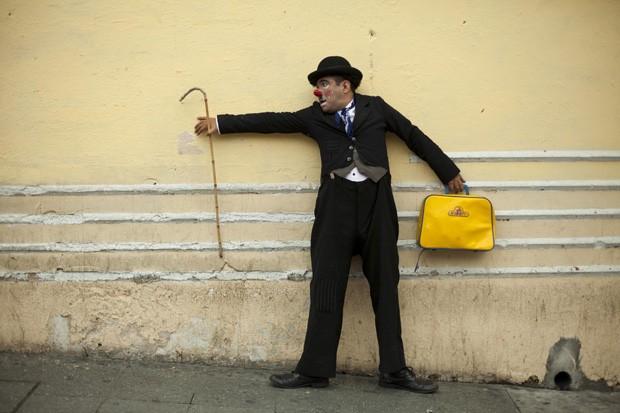 Palhaço vestido de Charlie Chaplin posa em parede durante evento na Cidade da Guatemala (Foto: Moises Castillo/AP)