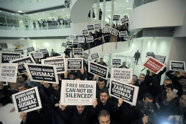 Pessoas se reúnem na sede do jornal 'Zaman', em Istambul, para protestar contra invasão e prisão de membros da imprensa ligada à oposição na Turquia  (Foto: AP Photo)