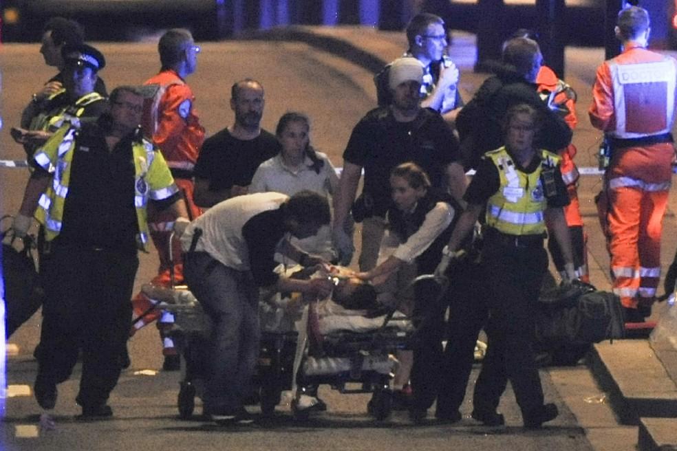 Pessoa ferida é levada em maca por médicos após ataque reivindicado pelo Estado Islâmico, em Londres (Foto: DANIEL SORABJI / AFP)