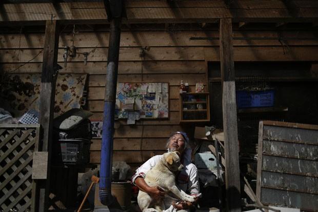Keigo Sakamoto segura um dos cães abandonados que ele cuida (Foto: Damir Sagolj/Reuters)
