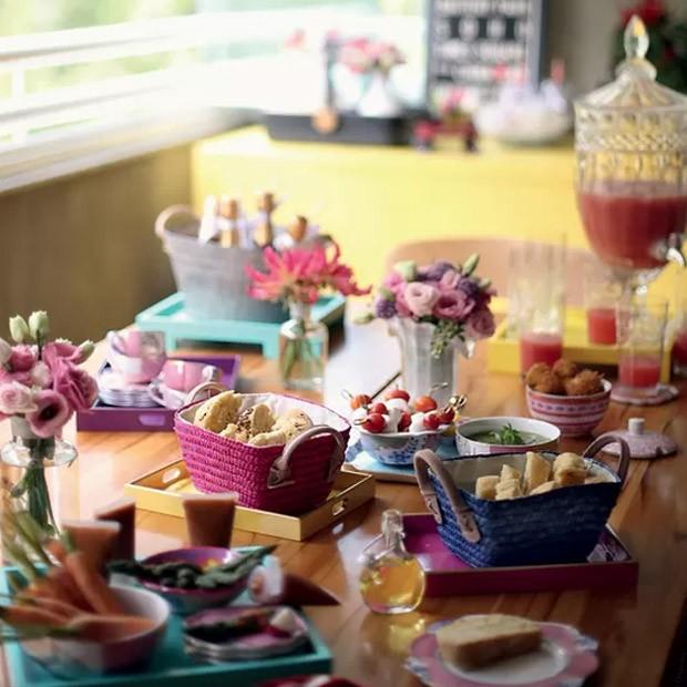 Cestinhas com pães caseiros, suqueira, copos e bowls foram colocados sobre bandejas coloridas, que alegraram a mesa e evitaram manchas na madeira (Foto: Rogério Voltan/ Editora Globo)