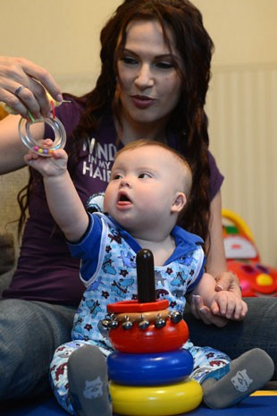 Bebê com síndrome de Down brinca com a mãe (Foto: Kirill Kudryavtsev / AFP)