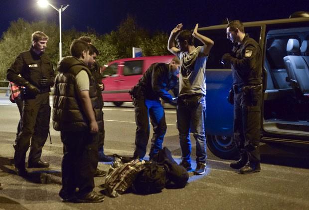 Imigrante sírio é revistado por policiais alemães neste domingo (13), na cidade de Freislassing, no sul da Alemanha, perto da fronteira com a Áustria (Foto: AFP Photo)